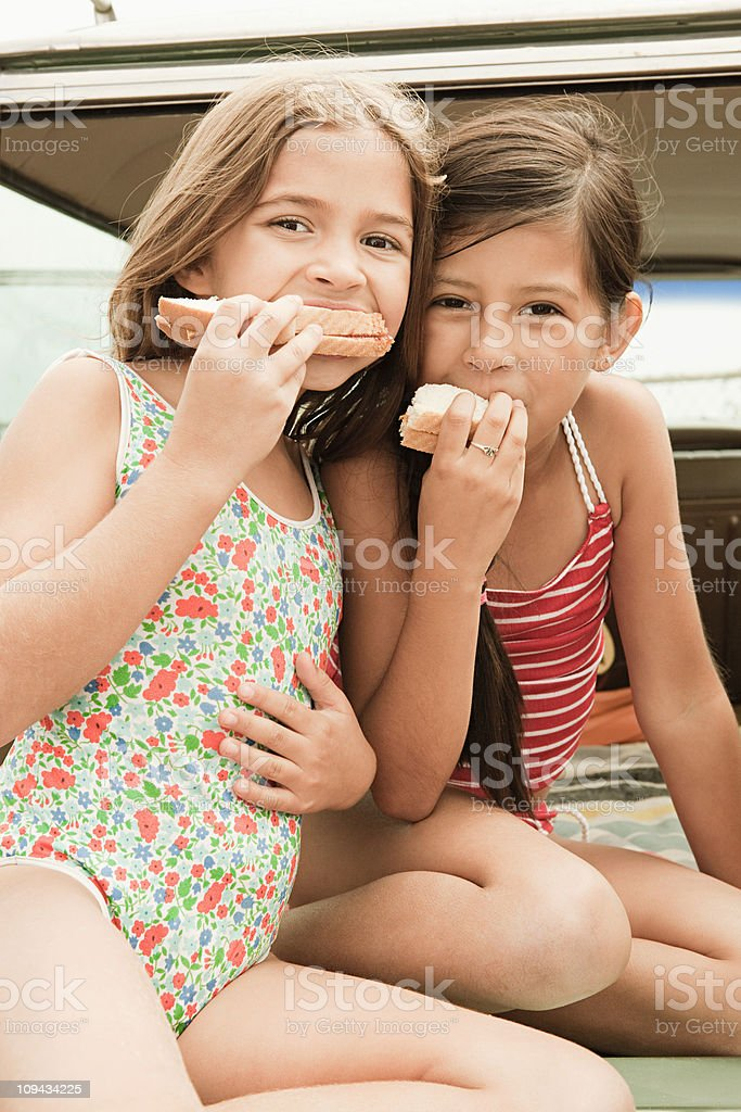 Two girls eating sandwiches on car boot royalty-free stock photo