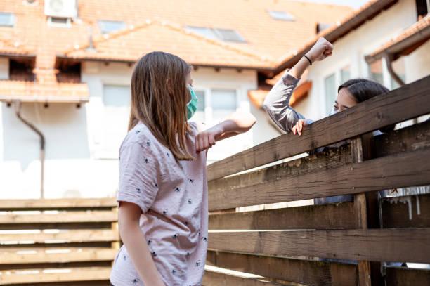 Zwei Mädchen Ellbogen stoßen über den hohen Holzzaun während Coronavirus Covid-19 – Foto