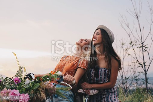 Two beautiful girls with bike smiling on a grat day