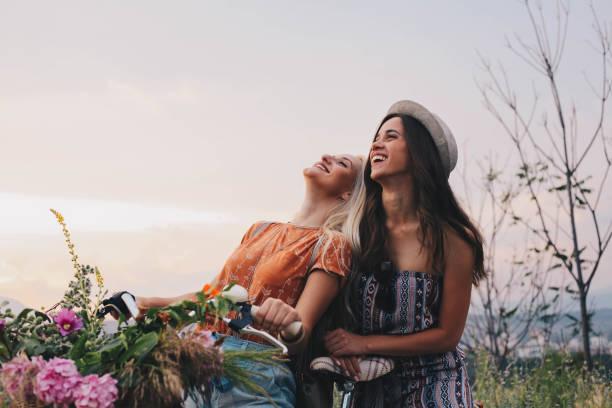 Dos chicas disfrutan de bici y el gran día - foto de stock