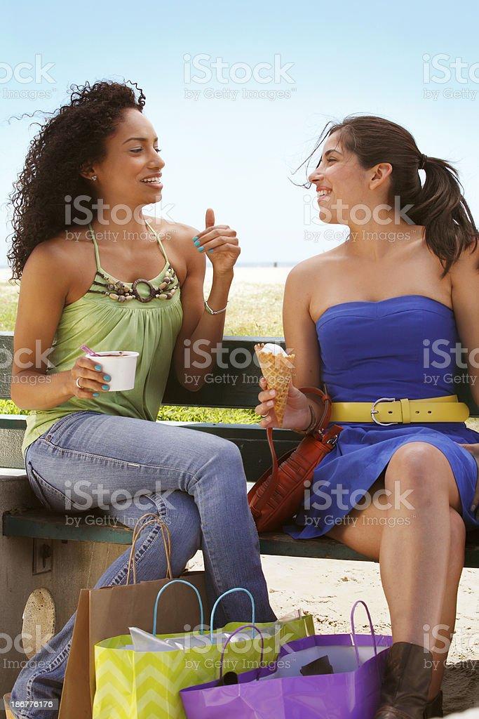Two girls enjoying ice cream after shopping royalty-free stock photo