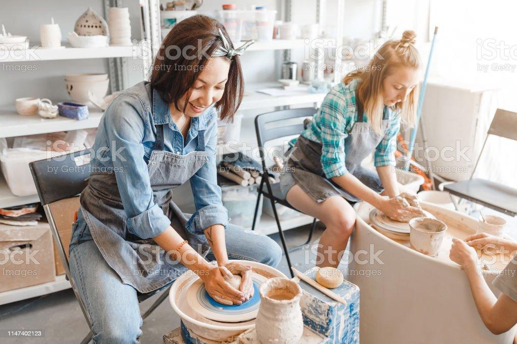 Dois amigos das meninas que sorriem e que falam ao trabalhar na roda dos Potters que faz a argila handmade ofício na oficina da cerâmica, na amizade e no conceito da orientação - Foto de stock de Amizade royalty-free