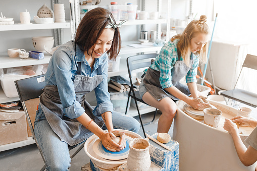 Two girls friends smiling and talking while working on potters wheel making clay handmade craft in pottery workshop, friendship and guidance concept