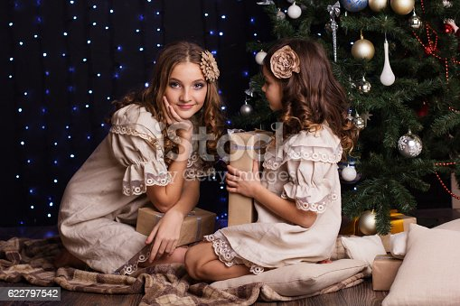 1061876006istockphoto Two girls friends with gifts near christmas tree 622797542
