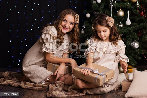 1061876006istockphoto Two girls friends with gifts near christmas tree 622797648