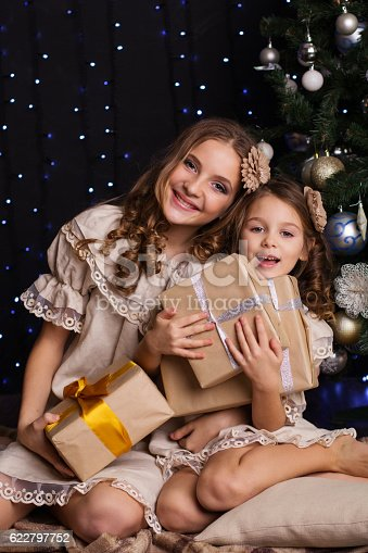 1061876006istockphoto Two girls friends with gifts near christmas tree 622797752