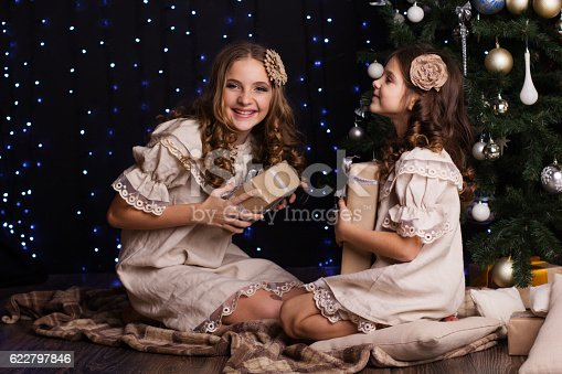 1061876006istockphoto Two girls friends with gifts near christmas tree 622797846