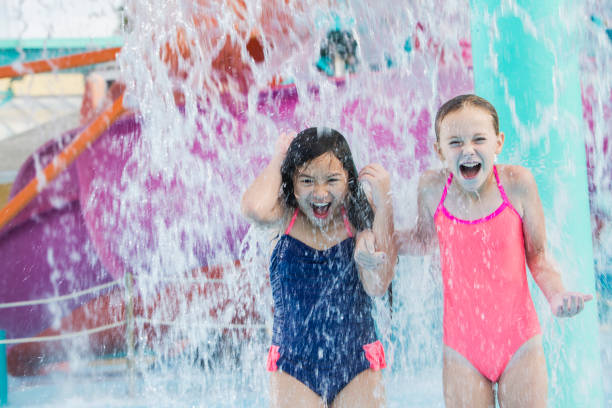 two girls getting drenched at water park - children play water park stock photos and pictures