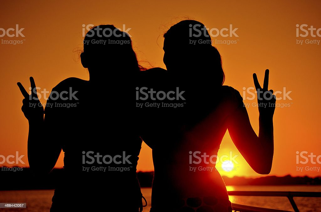 Two Girls Giving Peace Sign at Sunset by the Ocean stok fotoğrafı