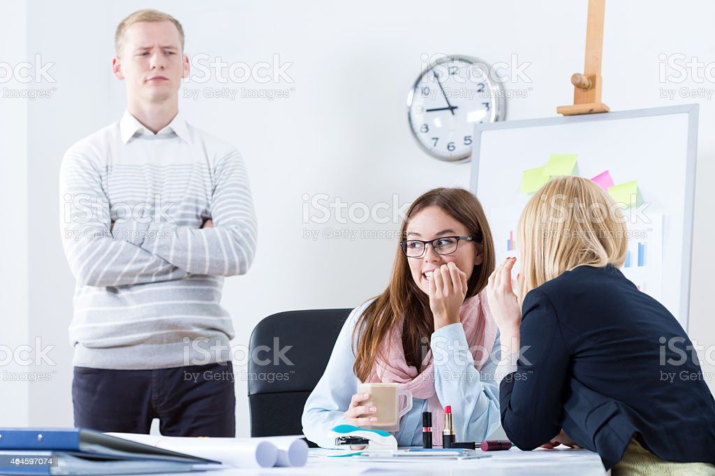 Two girls gossiping in the office with man looking over stock photo