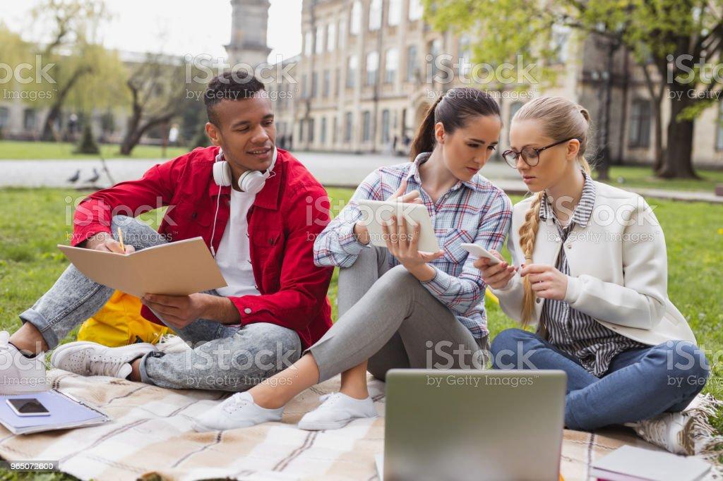 Two girls gossiping making home task with their fellow student zbiór zdjęć royalty-free