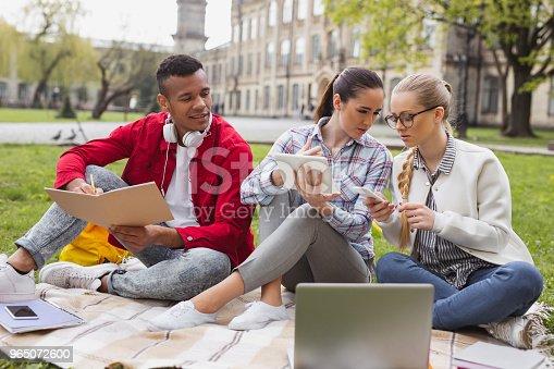Two Girls Gossiping Making Home Task With Their Fellow Student - Stockowe zdjęcia i więcej obrazów Badanie lekarskie