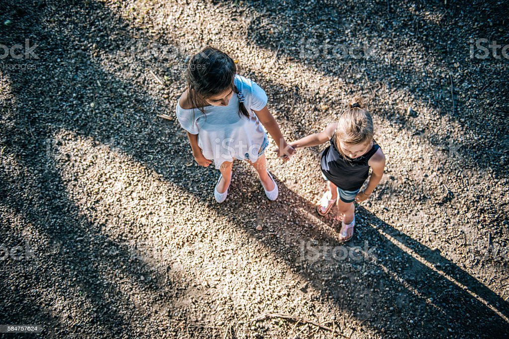 Two girls holding hands on playground stock photo