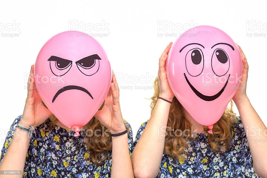 Two girls holding pink balloons with facial expressions stock photo