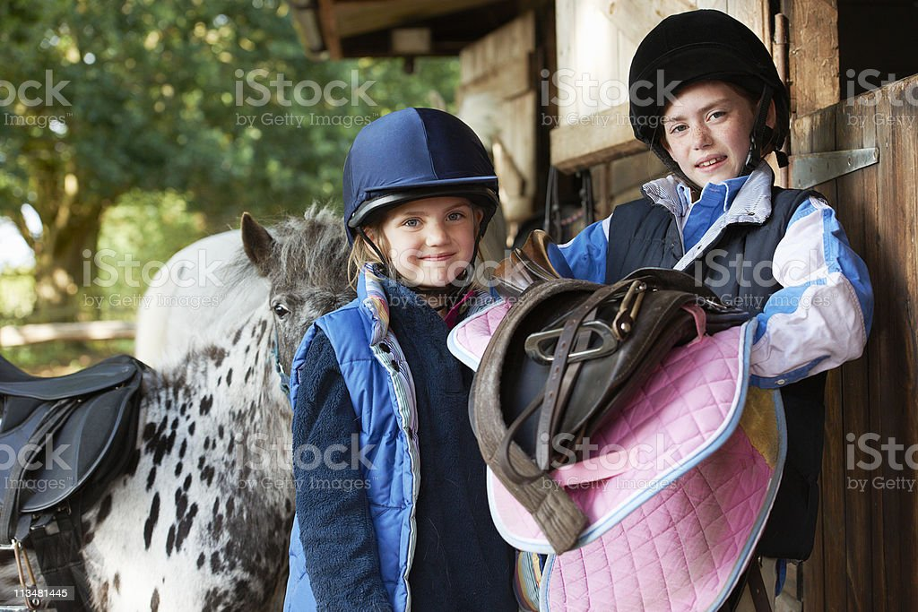 Two girls holding saddles with pony stock photo