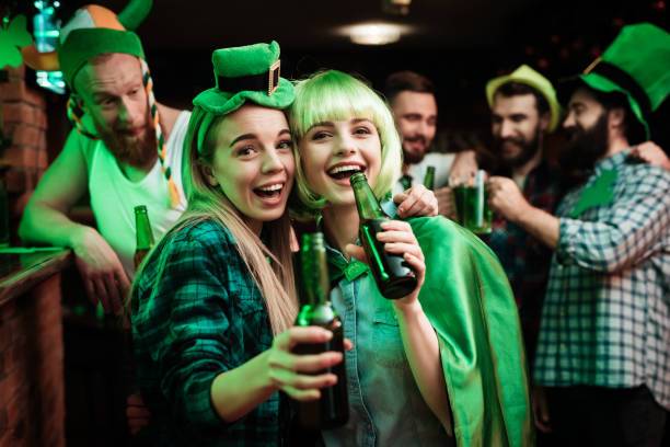two girls in a wig and a cap are photographed in a bar. - st patricks days stock photos and pictures