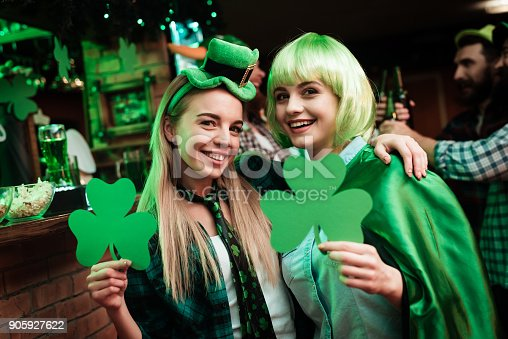 Two girls in a wig and a cap are photographed in a bar. They celebrate St. Patrick's Day. They are having fun. One girl is holding a clover.