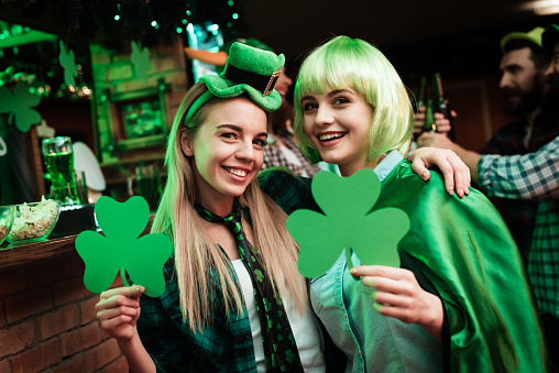 Two girls in a wig and a cap are photographed in a bar.