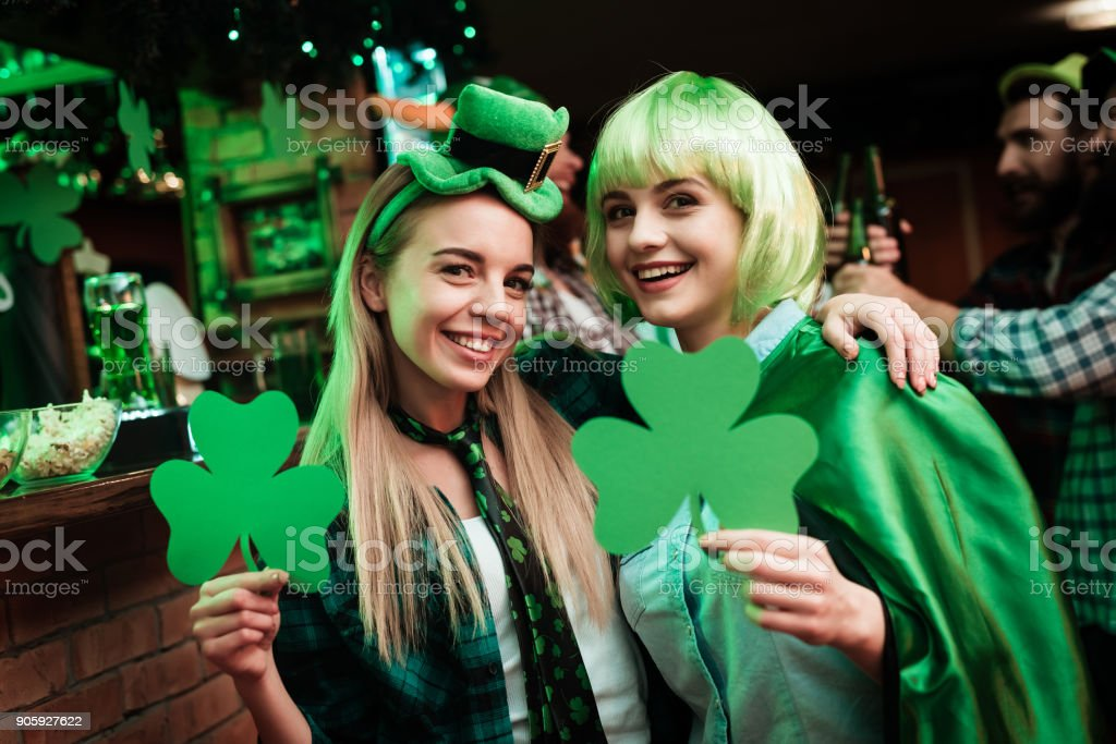 Two girls in a wig and a cap are photographed in a bar. stock photo