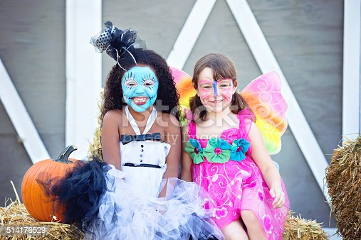 Two adorable girls dressed up as a doll and a butterfly sitting on a bale of straw at a Halloween party.