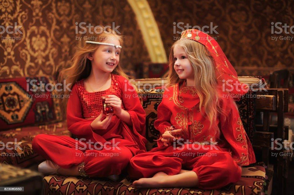 Two Girls In Folk Arabic Costumes Drinking Turkish Tea Together