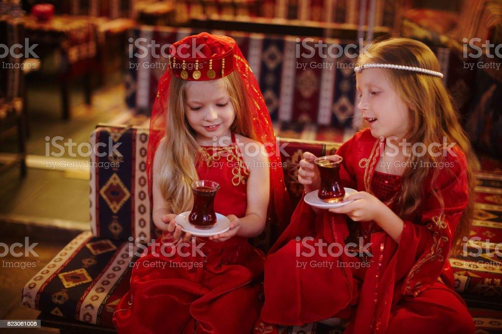 Two girls in folk Arabic costumes drinking Turkish tea together stock photo