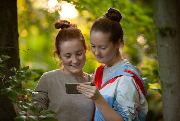 Two girls in forest setting, checking their social media on a smartphone stock photo