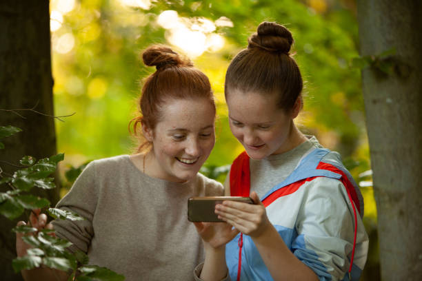 Two girls in outdoor forest setting, checking social media on a smartphone stock photo