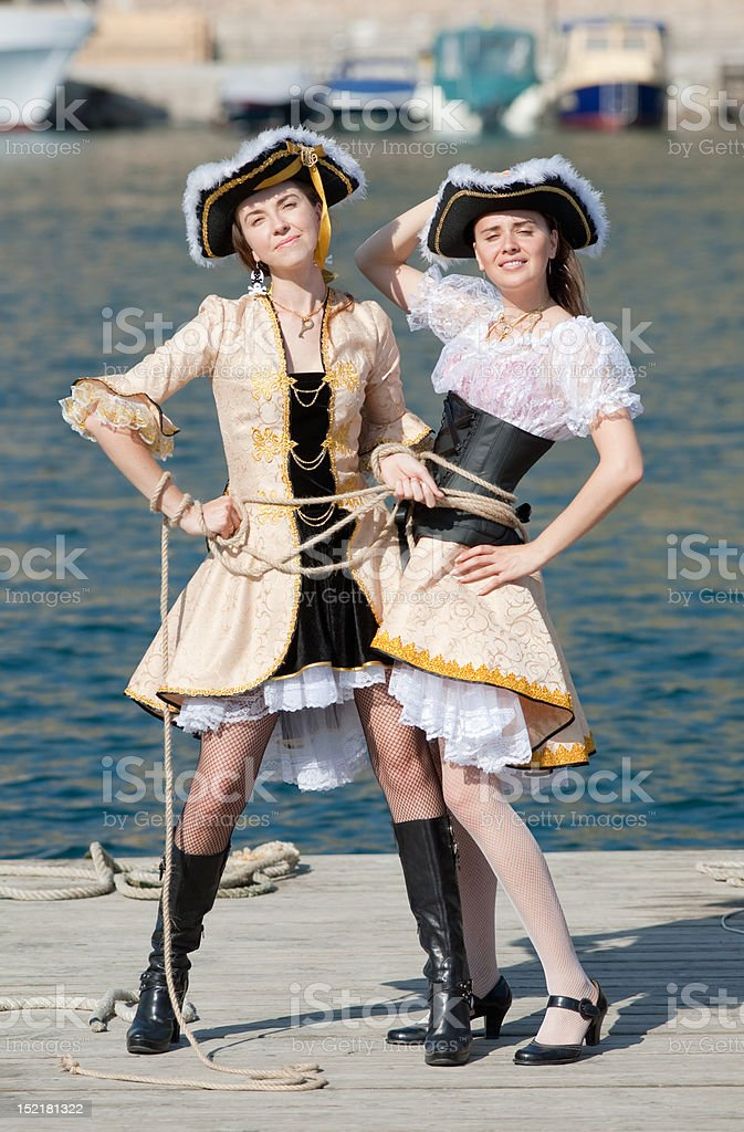Two girls in pirate costumes on the pier royalty-free stock photo