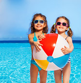Two cute smiling girls in swimwear and sunglasses holding big inflatable ball in their hands against of blue sky and sea