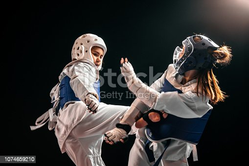 Two girls in taekwondo combat practicing martial arts and wearing full protective equipment, helmets and shields