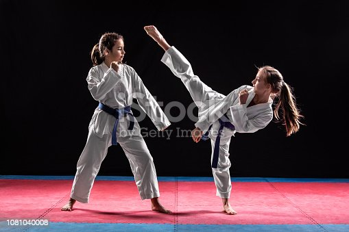 Two girls in taekwondo combat practicing martial arts. They wears kimonos