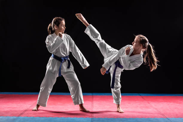 Two girls in taekwondo combat Two girls in taekwondo combat practicing martial arts. They wears kimonos karate stock pictures, royalty-free photos & images