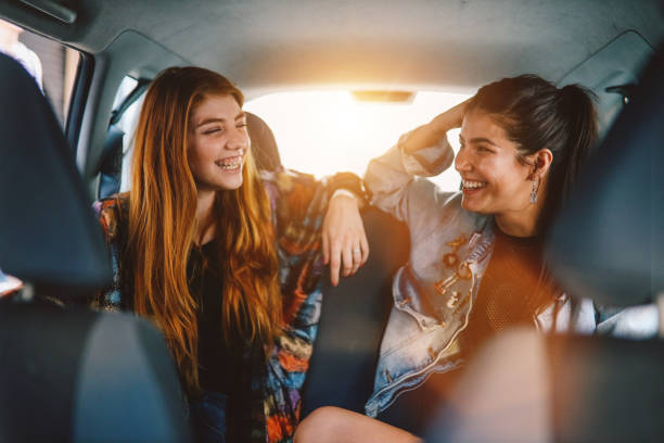 Two girls in the backseat of a ride share in Buenos Aires stock photo