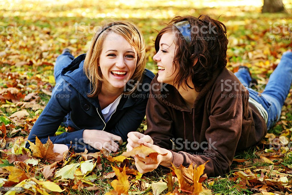 Two Girls Laughing and Laying in Leaves royalty-free stock photo