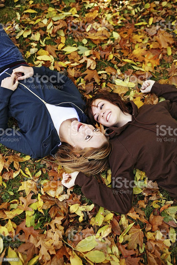 Two Girls Laying on Their Backs Looking at Each Other royalty-free stock photo