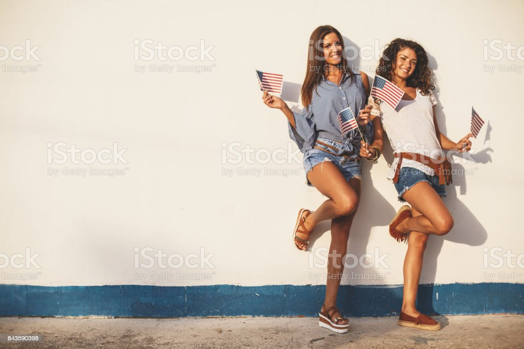 Two girls leaning on a wall stock photo