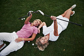 Two girls lie on the golf course and relax after the game
