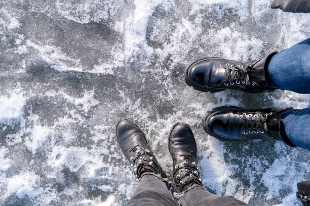 Two girls Looking down at feet. Frozen lake or river. Feet on ice. Wearing snow shoes and standing on the clear big ice in Iceland stock photo