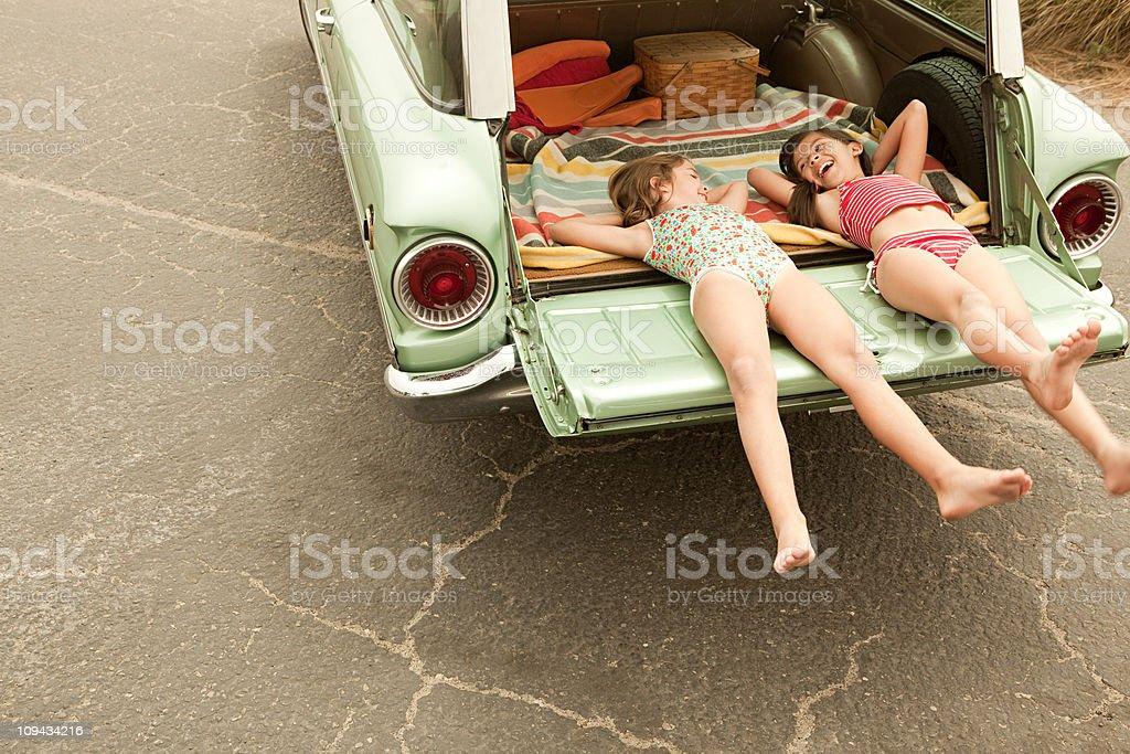 Two girls lying in estate car stock photo