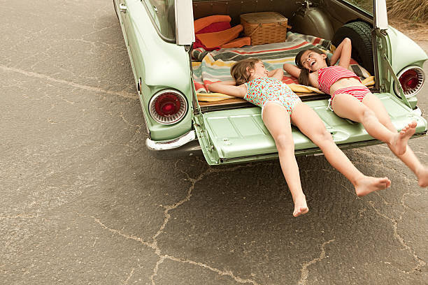 Two girls lying in estate car stock photo