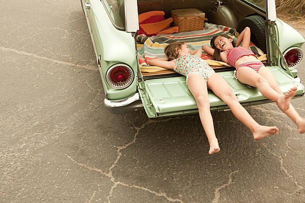Deux filles allongé en voiture de la propriété - Photo