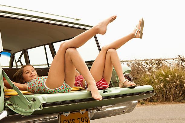 zwei mädchen liegen in estate auto mit beine in der luft - kinderfüße stock-fotos und bilder