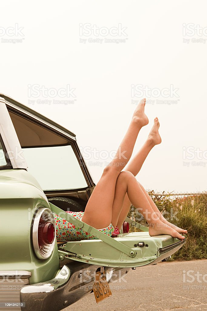 Two girls lying in estate car with legs in the air royalty-free stock photo