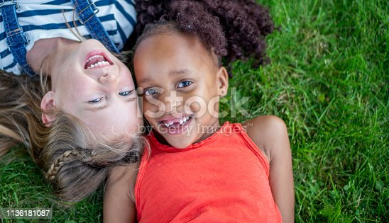 Two kindergarten-aged girls lie on the grass in a park, smiling.