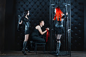 男性 2 つの女の子 mistress 建っています。