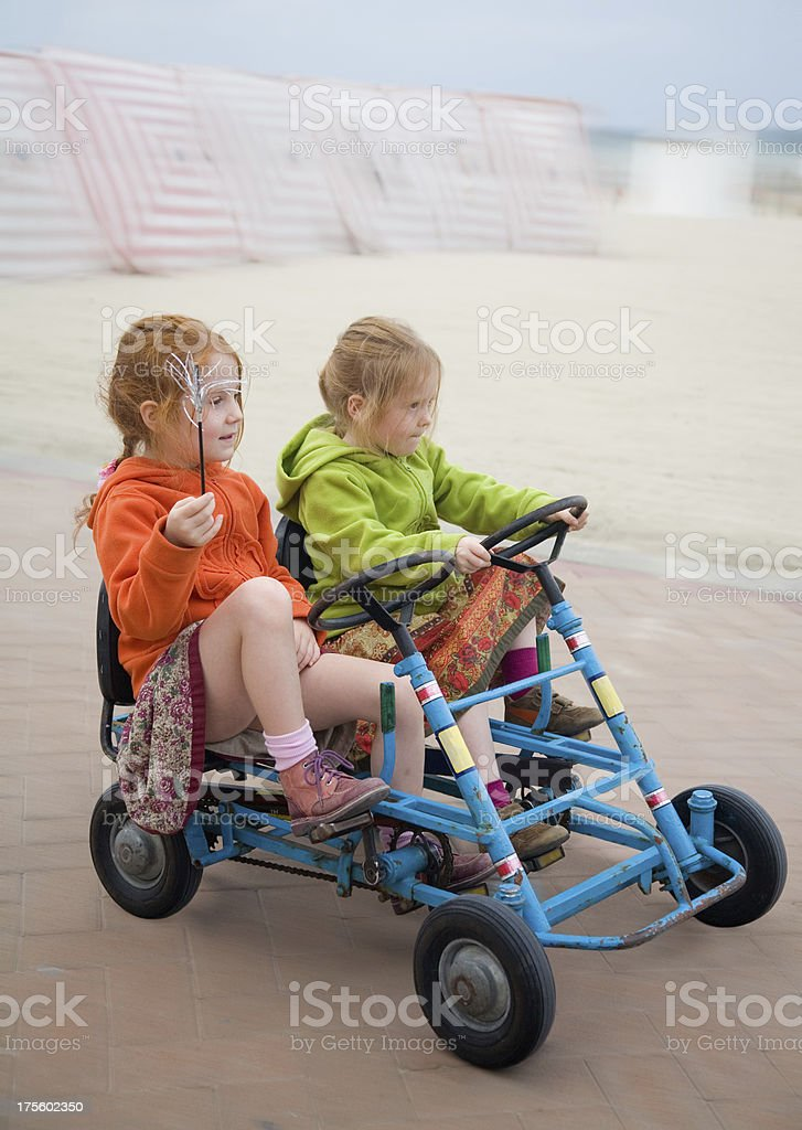 Two girls on a go-cart at the beach royalty-free stock photo