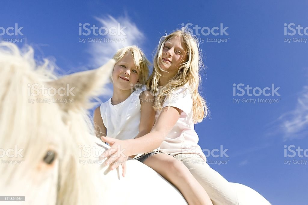 two girls on a horse stock photo