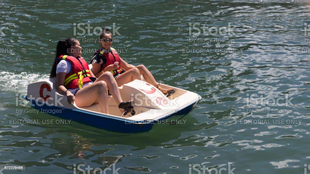 Dos chicas en un barco a pedales. - foto de stock