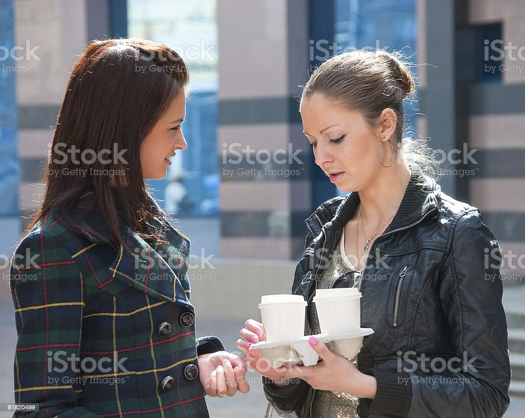 Two girls on a street with coffee royalty-free stock photo